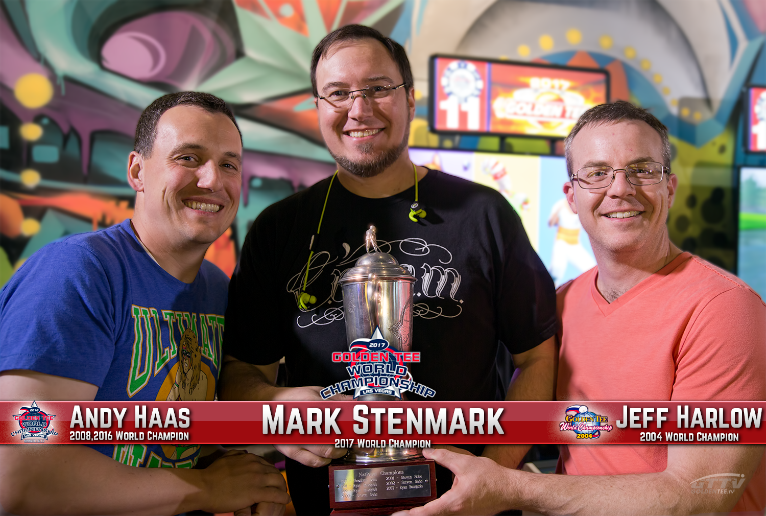 Former World Champions Andy Haas (left) and Jeff Harlow (right) hold up the Hodgson-Zielinski trophy with the 2017 Champion, Mark Stenmark